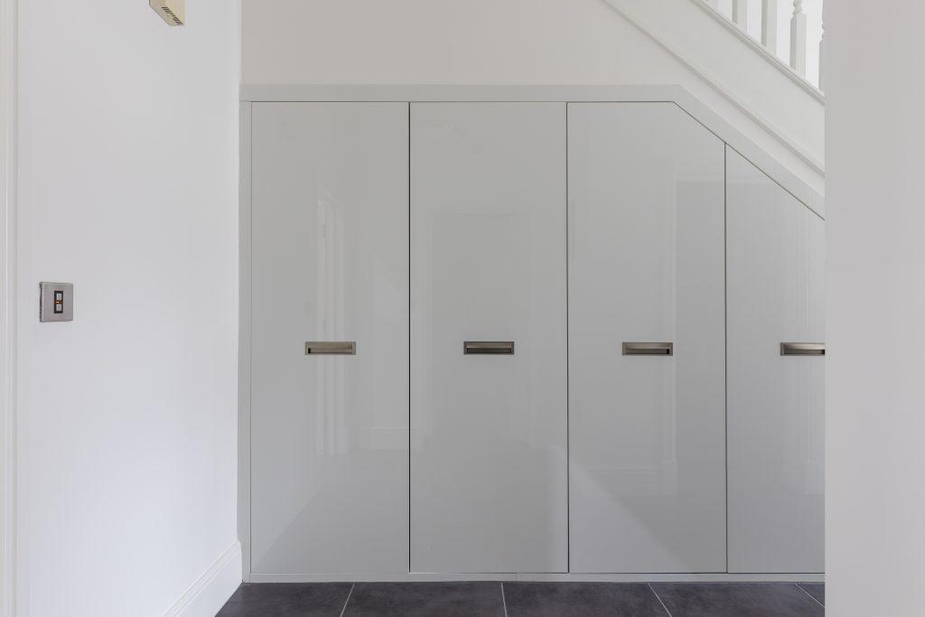 high gloss white undet stairs storage