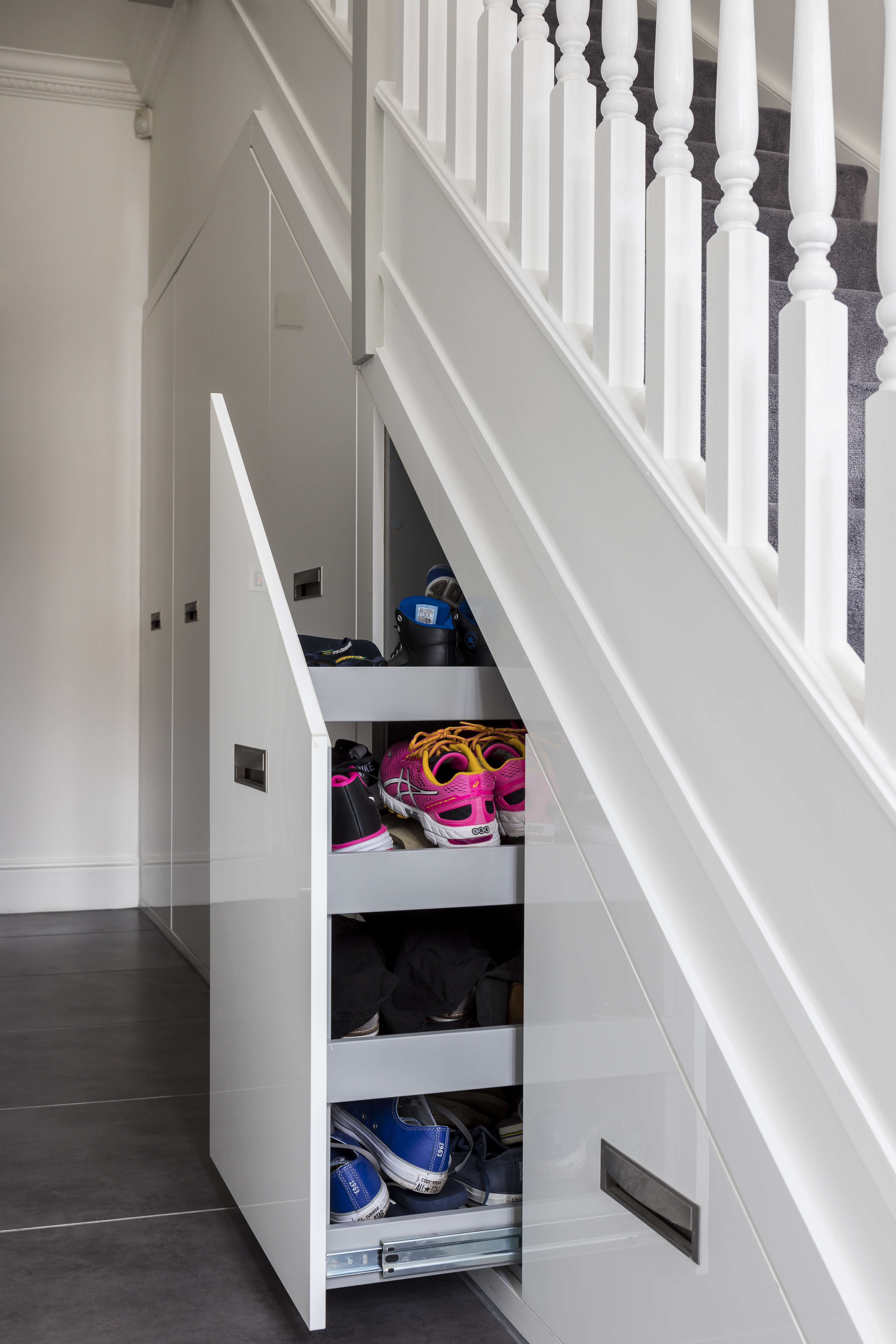 High gloss white under-stairs cabinets
